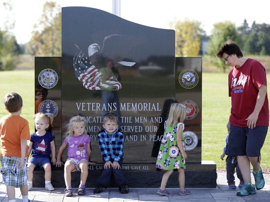 Marion Daycare worker Beth Allen checks out a section of the new veterans memorial with her group Friday at Veterans Park in Marion.