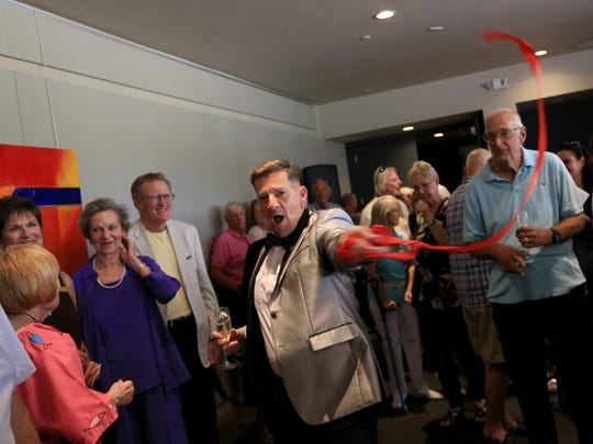John Yohman swings a ribbon from the dedication ceremony