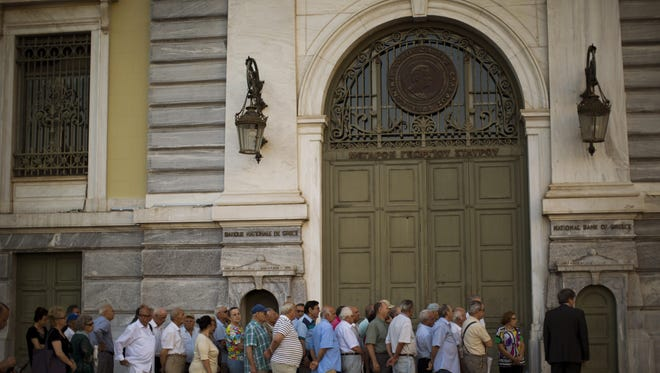 Pensioners wait outside the main gate of the national bank of Greece in central Athens on Friday.