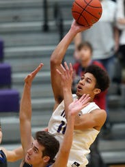 Kai Warren shoots over Olympic's Keaton Dean during a Dec. 12 game in Poulsbo.