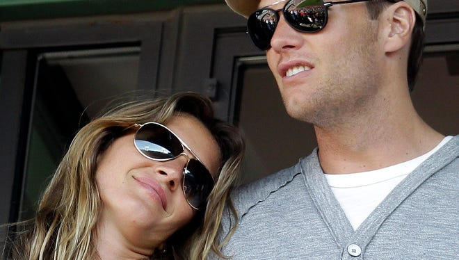 Supermodel Giselle Bundchen, left, rests her head on the shoulder of her husband, New England Patriots quarterback Tom Brady, as they stand in a box during a baseball game between the Boston Red Sox and the New York Yankees at Fenway Park in Boston, Friday, April 20, 2012.