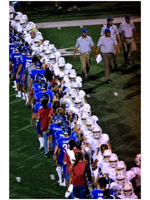 Members of the Cooper High School Cougars and the Frenship High School Tigers shake hands after Friday's game at Shotwell Stadium Sept. 22, 2017. Cooper won, 62-3.