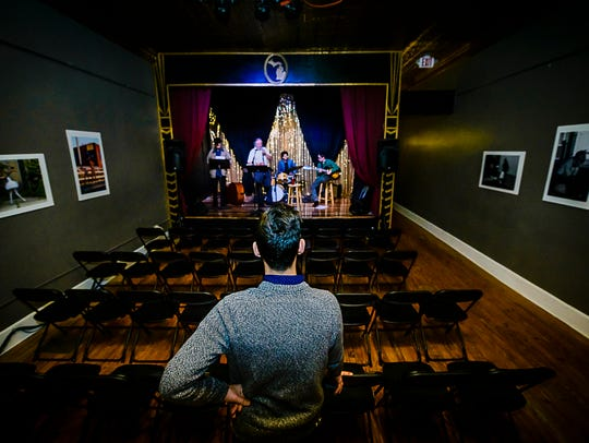 Dylan Rogers, owner of the Robin Theatre, listens as