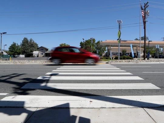 A car passes through a crosswalk on Cypress Avenue.