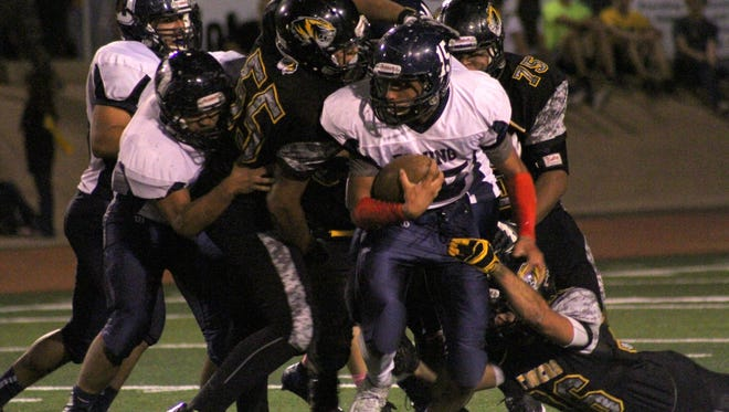 Dante Urrea is tackled by a pack of Tiger defenders Friday night at Tiger Stadium.