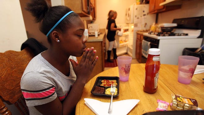 Brandy Robertson, 13, says a prayer before eating while her grandmother Joyce Robertson gets items from the kitchen. Robertson is feeding herself and her two granddaughters on $99 per month with help from the state.