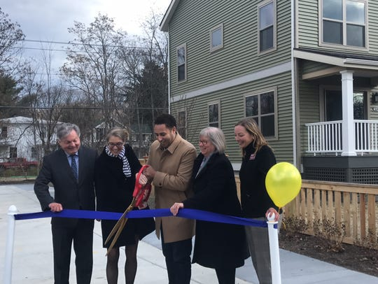 Ithaca Mayor Svante Myrick cuts the ribbon at the new affordable housing project at 210 Hancock Street. From left to right: Paul Mazzarella, Executive Director of Ithaca Neighborhood Housing Service; NYSHCR Commissioner RuthAnne Visnauskas; Ithaca Mayor Svante Myrick; District 125 Assemblywoman Barbara Lifton; INHS Executive Director Johanna Anderson.