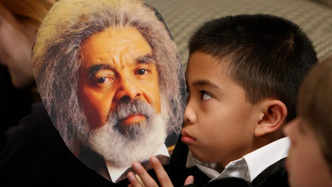 Angelo Madrilejos, a fourth-grader at Our Lady of Victory school in Washington, D.C., listens to a Frederick Douglass re-enactor give a presentation on the anti-slavery activist as part of Black History Month on Feb. 14, 2008.