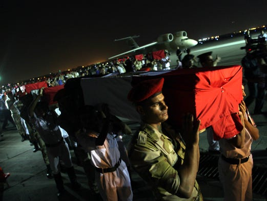 Egyptian military and policemen carry coffins with the bodies of off-duty policemen who were killed near the border town of Rafah, North Sinai. Islamic militants ambushed two mini-buses carrying off-duty policemen, killing more than two dozen of them.