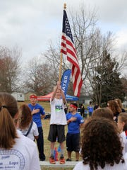 The National Anthem is played as students from Bethel Elementary School get ready to start the Boosterthon Color Run.