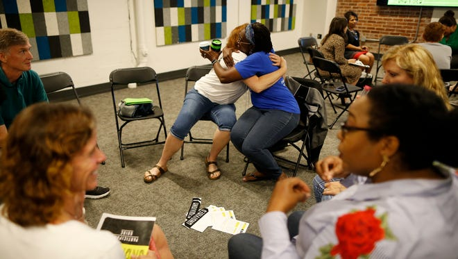 Connie Carroll, left, who lives in the Cincinnati neighborhood of Madisonville, and Kimberly Elliott, of Green Hills, Ohio, hug after a discussion about implicit racial bias during a meeting May 16, 2018, of the Undivided group at Crossroads Church in the University Heights neighborhood of Cincinnati.