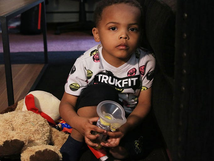 Zaviyon Scott, 4, holds one of his inhalers, which