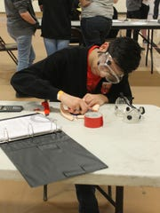 Andre Gonzalez from Centennial High School in Las Cruces works on his Wind Turbine design at the 2016 Science Olympiad.