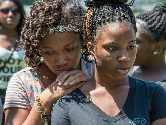 Aa'myah Moore, 12, and Zykeya Briddell, 15, both of Salisbury, comfort each other at a vigil honoring Rakim Russell at Doverdale Park in Salisbury.
