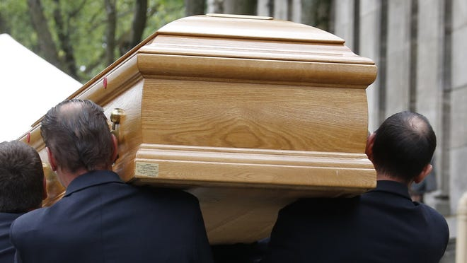 Pallbearers carry the coffin of French singer and composer Georges Moustaki on May 27, 2013.