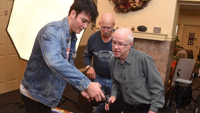 From left, Jerrod Noble, Bill Nourse and Tony Bennett discuss exposure and lighting before taking portraits of residents on Tuesday at Namaste House Assisted Living in Farmington.
