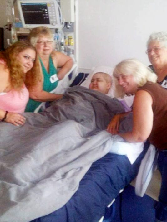Family members gather around Brandon Bishop, 13, recently while in the hospital. Bishop passed away Sept. 5 after a with Medulloblastoma, a form of brain cancer.