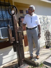 "Morris Taft Thomas shows off his ""Family"" sculpture in front of his artwork storage area behind his home in Alexandria."