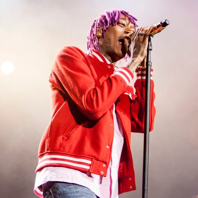 Gripping a gold microphone, rapper Wiz Khalifa performs