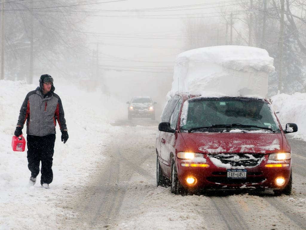 A man walks with a gas can along Como Park Blvd. in Lancaster, N.Y. as he looks at a minivan go by with snow on its roof.