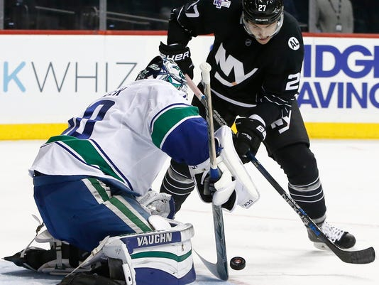 New York Islanders center Anders Lee (27) shoots against Vancouver Canucks goalie Ryan Miller, left, in the second period of an NHL hockey game in New York, Sunday, Jan. 17, 2016. (AP Photo/Kathy Willens)