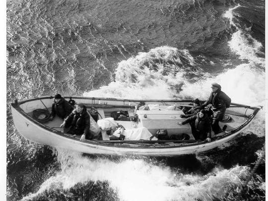 """With William """"Ed"""" Kiely (far right, standing) in charge, the Yakutat's surfboat brings back two survivors off the sinking S.S. Fort Mercer."""