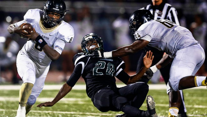 Whitehaven quarterback Lesley Mosby (left) scrambles past Cordova defender Kentrell Torrance (middle) after receiving a block from teammate Anthony Geter (right) during second quarter action of their Region 4-6A football game.
