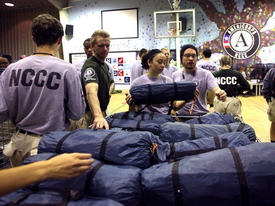 AmeriCorps NCCC members gather tents in the gymnasium