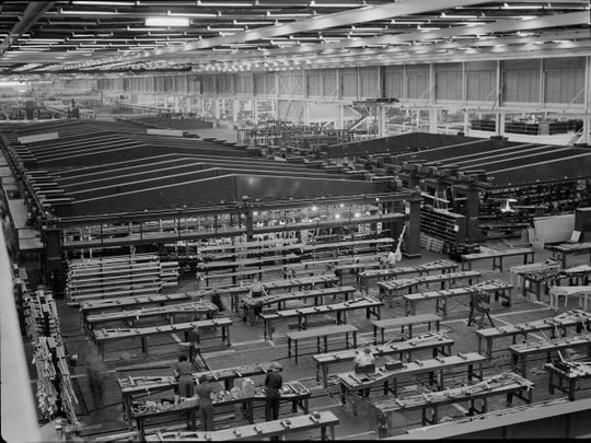 Fixtures in background hold bomber wings during assembly at Ford's vast Willow Run plant during World War II.