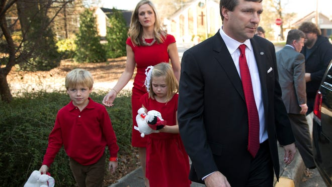 Alabama defensive coordinator Kirby Smart is followed by his wife Mary Beth and seven-year-old twins Weston and Julia to a waiting car after a press conference where he was introduced as Georgia's new NCAA college head football coach  Monday, Dec. 7, 2015, in Athens, Ga. Smart will continue in his current role as Alabama's defensive coordinator through the College Football Playoff as he also begins work as Georgia's coach. (AP Photo/John Bazemore)