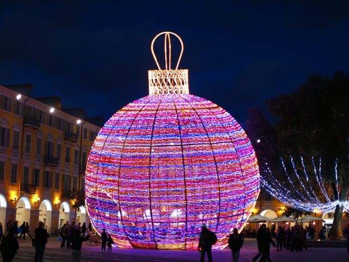 People walk by a giant christmas ball displayed in Nice, southeastern France, on December 4, 2013.        AFP PHOTO / VALERY HACHE        (Photo credit should read VALERY HACHE/AFP/Getty Images)