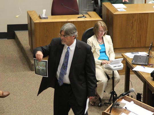 Chief Assistant Public Defender Andy Thomas shows a Wakulla County jury family photos of defendant Andrew Wilson Friday.