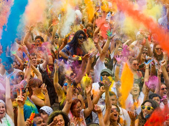 Revelers of the Holi Festival of Colors throw colored powders in the air in Madrid, Spain, Saturday, Aug. 9, 2014. The festival is fashioned after the Hindu spring festival Holi, which is mainly celebrated in the north and east areas of India. (AP Photo/Daniel Ochoa de Olza)