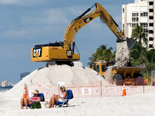 An excavator moves sand around on Park Shore Beach during a Collier County beach renourishment project using dump trucks on Wednesday, Nov. 2, 2016.