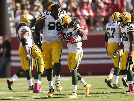 Packers nose tackle Letroy Guion (98) and cornerback Sam Shields (37) celebrate following an interception against the 49ers at Levi's Stadium.