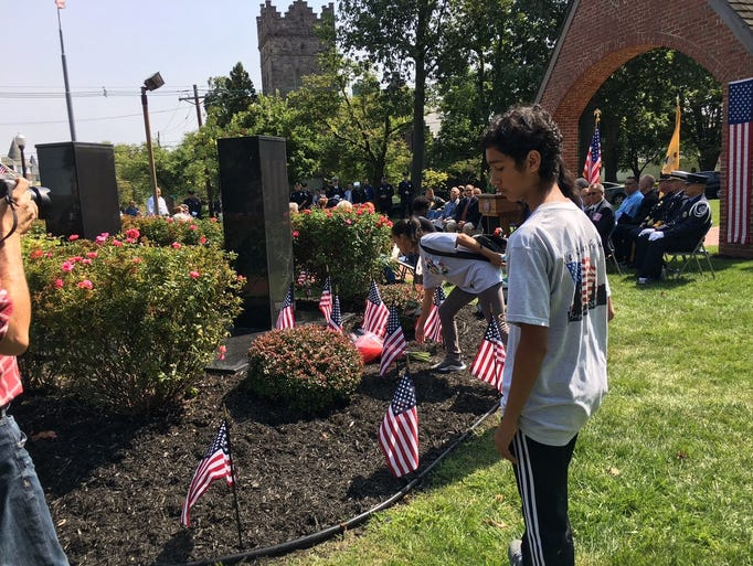 Lynnette Rivera places flowers at the Perth Amboy Twin