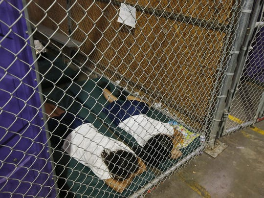In this June 18, 2014 file photo, two female detainees sleep in a holding cell, as the children are separated by age group and gender, as hundreds of mostly Central American immigrant children are being processed and held at the U.S. Customs and Border Protection Nogales Placement Center in Nogales, Ariz.  President Donald Trump has seized on an error by liberal activists for tweeting photos of detainees at the U.S.-Mexico border in steel cages and blamed the current administration for separating immigrant children from their parents.  The photos were taken by The Associated Press in 2014, when President Barack Obama was in office.