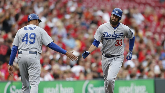 Los Angeles Dodgers' Scott Van Slyke, 33, is congratulated on his solo home run off Cincinnati Reds' Tony Cingrani by third base coach Lorenzo Bundy during the second inning.