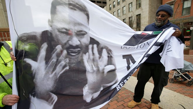 Steve Coachman, of Boston, right, unfurls a flag featuring a likeness of Martin Luther King Jr. on April 2, 2018 before a remembrance ceremony on City Hall Plaza in Boston. Dozens of speakers aged 5 to 91 took turns reading short passages from King's last speech during the remembrance. King originally delivered the speech in Memphis, Tenn. on the eve of his April 4, 1968 death.
