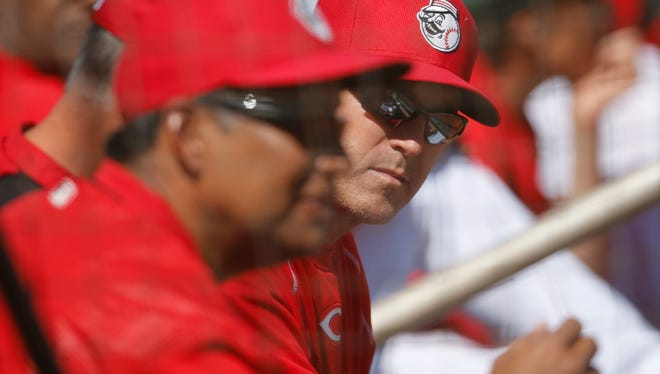 Reds manager Bryan Price, right, leans over to talk to coach Freddie Benavides during spring training.