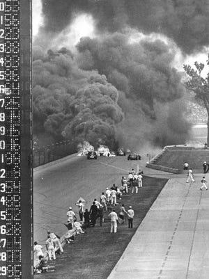 Cars can be seen still afire as smoke boils up after the fatal pieup at the north end of the main stretch during the 1964 Indianapolis 500.