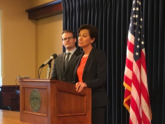 Gov. Kim Reynolds, right, talks with reporters at the