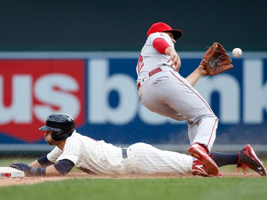 Minnesota Twins' Brian Dozier, left, safely steals second base as Los Angeles Angels shortstop Andrelton Simmons, right, gets the late throw from home plate during the fifth inning of a baseball game in Minneapolis, Saturday, April 16, 2016. The Twins won 6-4. ( AP Photo/Ann Heisenfelt)