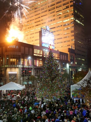 People crowd Fountain Square as fireworks light up the sky during the 2016 Macy's Light Up the Square event.