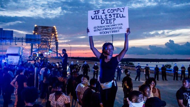 Chanel Trice holds a sign while standing on the cement median between the Eastbound and Westbound lanes of the Interstate 40 bridge over the Mississippi River. Black Lives Matter supporters brought traffic to a standstill on both sides of the bridge by about 7 p.m. as the estimated crowd on the bridge swelled to more than 1,000.