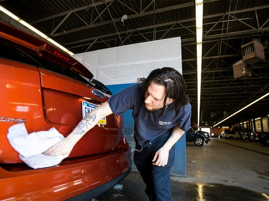 Beasley Ford Lincoln employee Jeremy Axe, details a 2007 Ford Edge Tuesday, March, 8, 2016, in Springettsbury Twp. Dealerships in York and nationwide have reported a small increase in new car leases and consumers trending toward larger vehicles, including SUVs and trucks. Amanda J. Cain photo