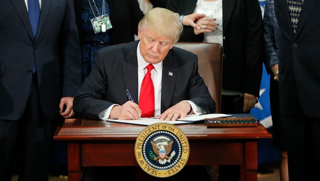President Donald Trump signs an executive order for border security and immigration enforcement improvements at the Department of Homeland Security on Jan. 25, 2017.