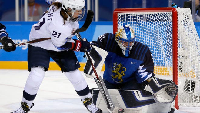 Noora Raty of Finland blocks a shot by Hilary Knight of the United States during a women's hockey preliminary round game Sunday.