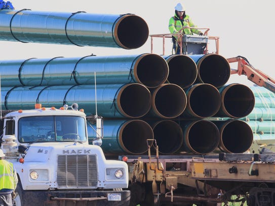 Workers unload pipes for the proposed Dakota Access