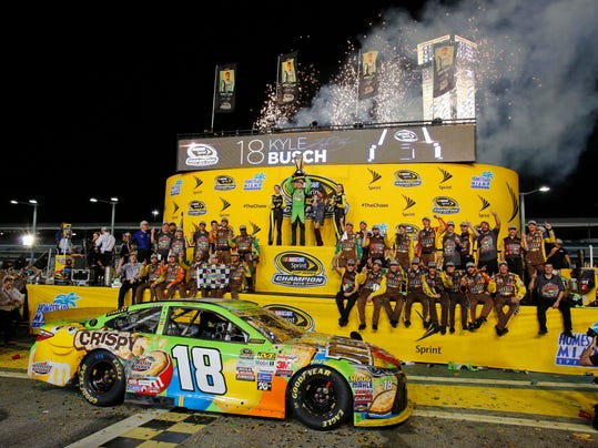 Kyle Busch raises his trophy after winning the NASCAR Sprint Cup Series auto race and the season title Sunday, Nov. 22, 2015, at Homestead-Miami Speedway in Homestead, Fla. (AP Photo/Terry Renna)